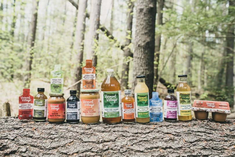Vermont Village vinegar products and applesauce on a log in the forest