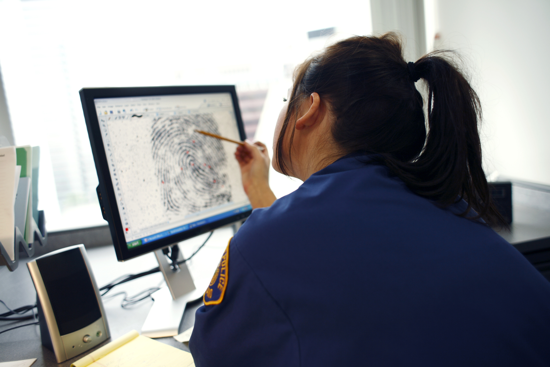 Cop at computer analyzing fingerprint