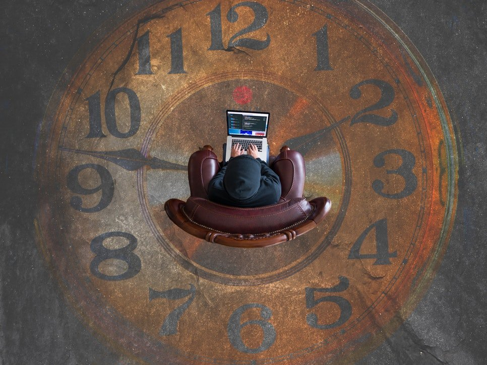 Individual with laptop sitting at the center of large clock face painted on floor