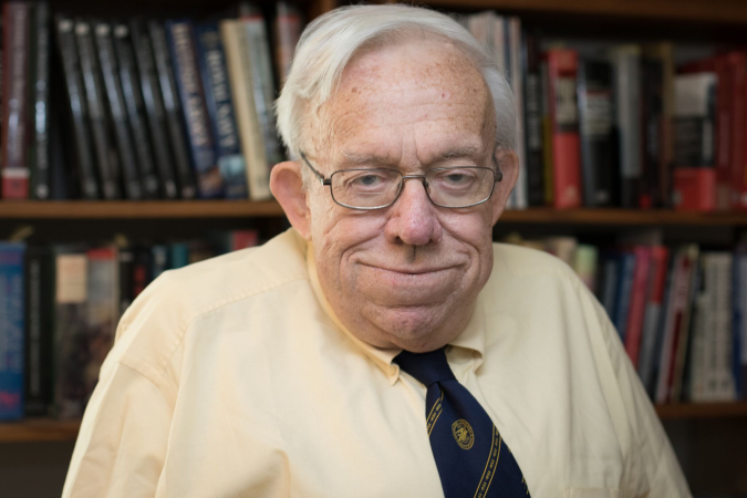 dennis showalter in yellow shirt and blue tie, in front of library bookcase