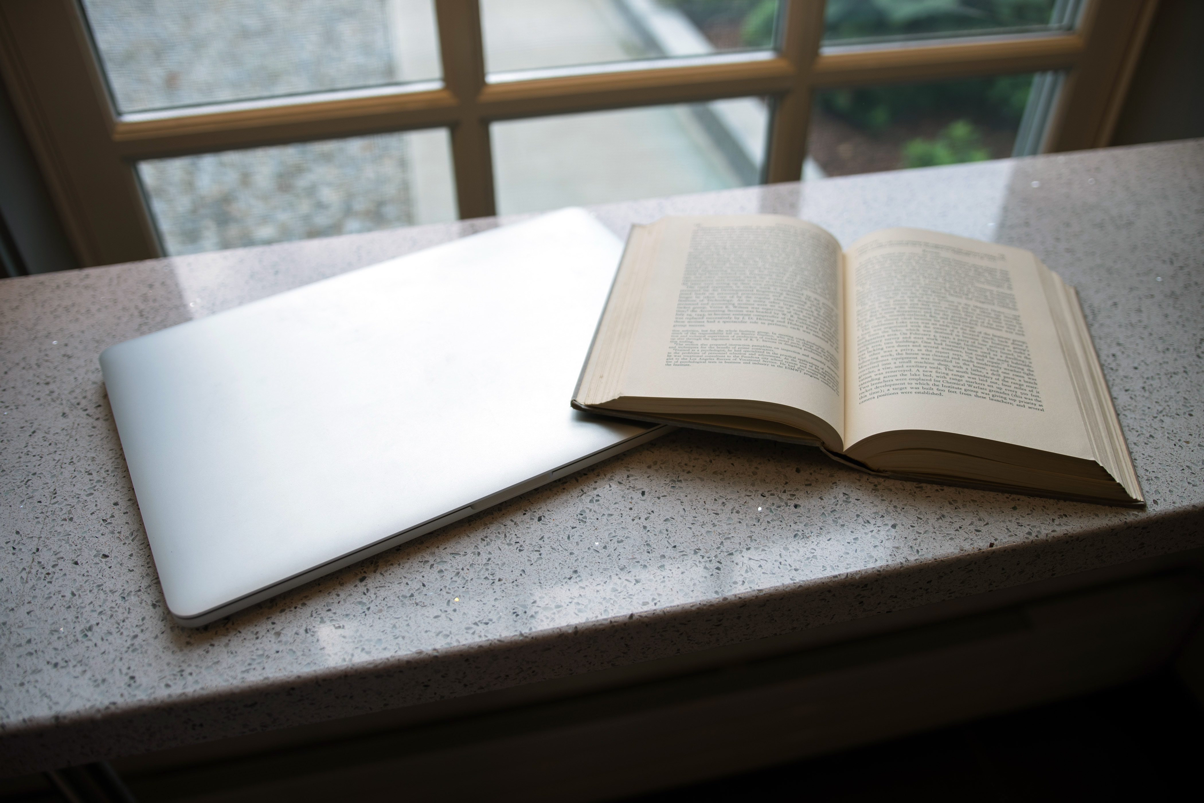 open book and closed laptop on top of desk overlooking a window