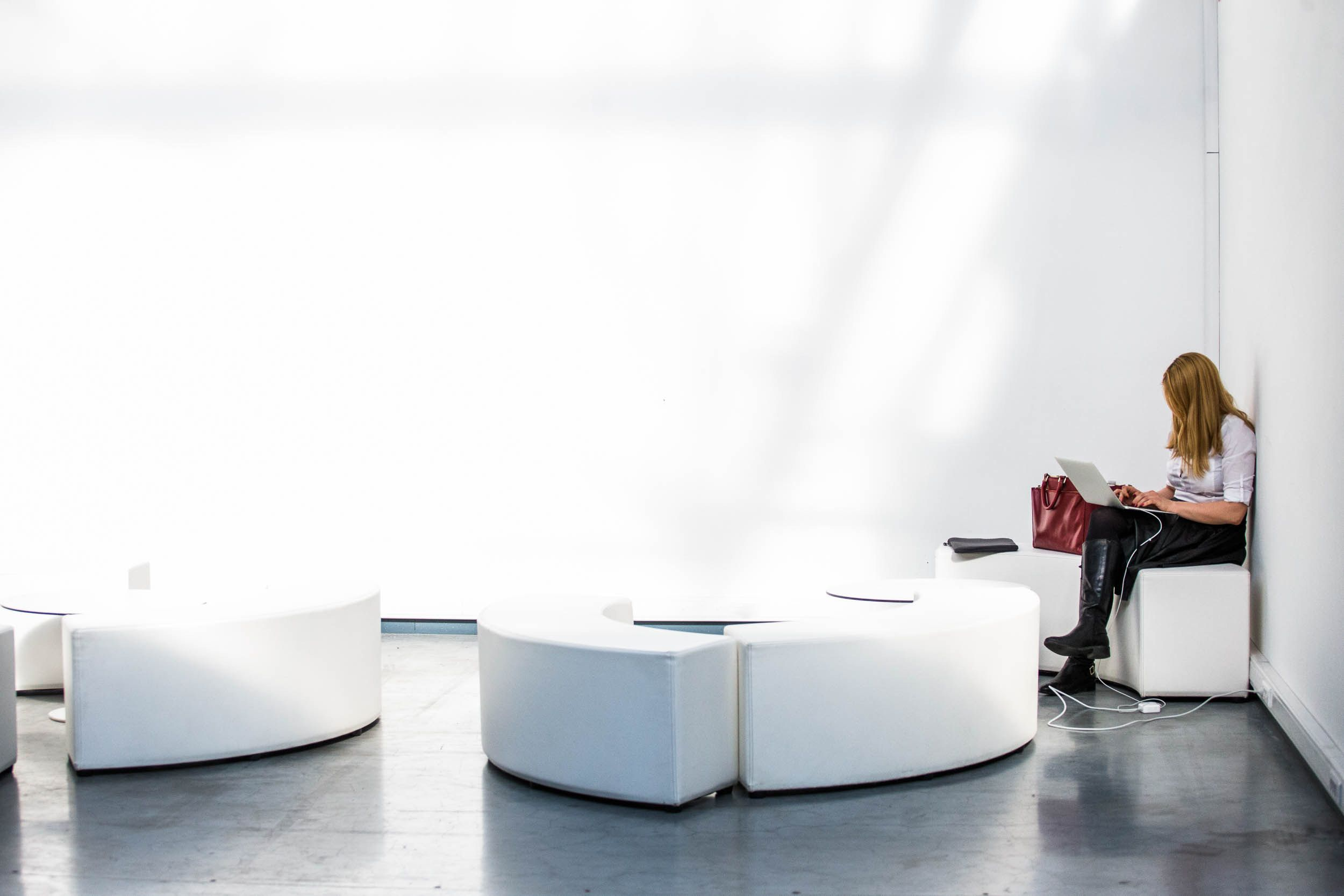 woman on laptop, white room