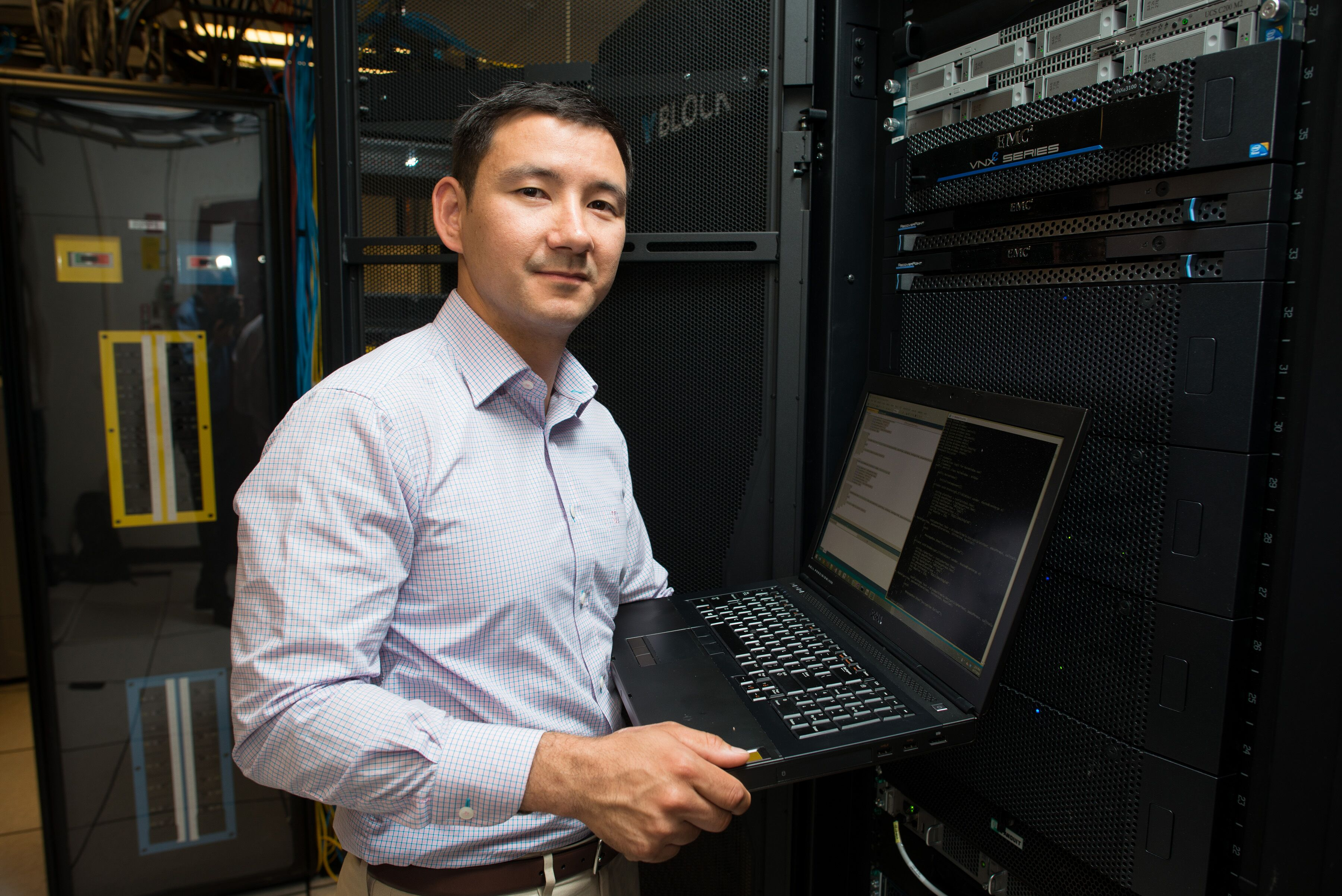 student holding laptop in server room